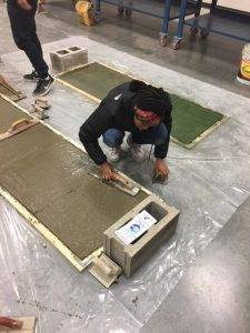 A student finishes a concrete slab, with help from a Cement Masons Local 132 apprentice, at the Columbus/Central Ohio Building Trades Job Fair