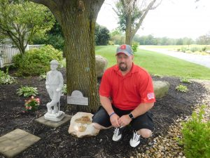 Daniel Poteet, Insulators Local Business Manager, kneels by the memorial for his father Donnie, prior to the Breadth of Life Golf Outing.